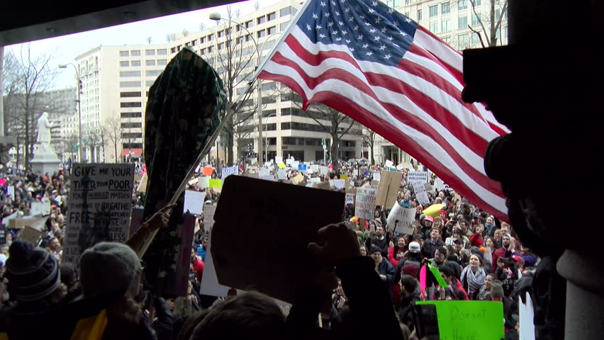 A flag waves as a crowd chants during a protest at Trump International Hotel in Washington, D.C. Jan. 29, 2017.