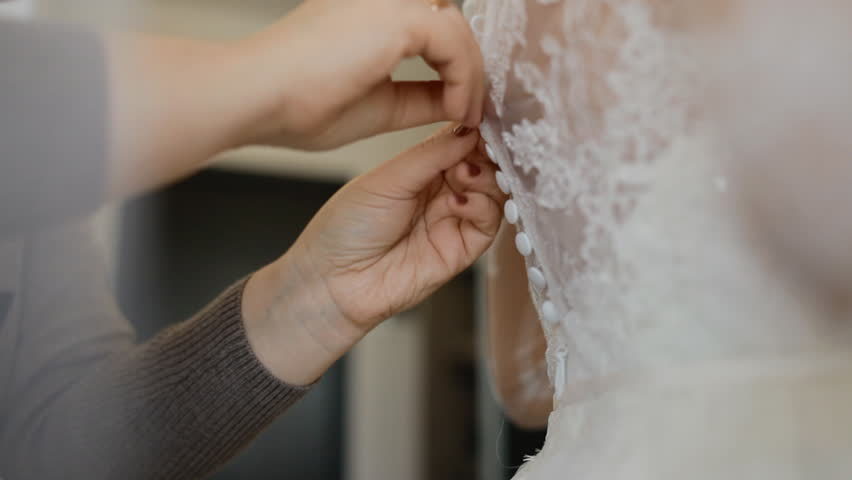 Mother helps the bride to fasten the buttons on the wedding dress | Shutterstock HD Video #26867062