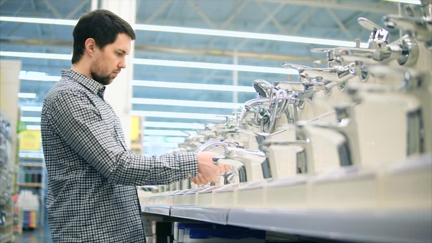 Sanitary engineering shop. Rows of taps and man customer. He switching faucet and checking its quality and design. | Shutterstock HD Video #26868460