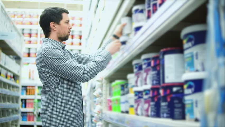 Man in dye shop. Rows of shelves with paint cans. He looking on can and reads label | Shutterstock HD Video #26868502