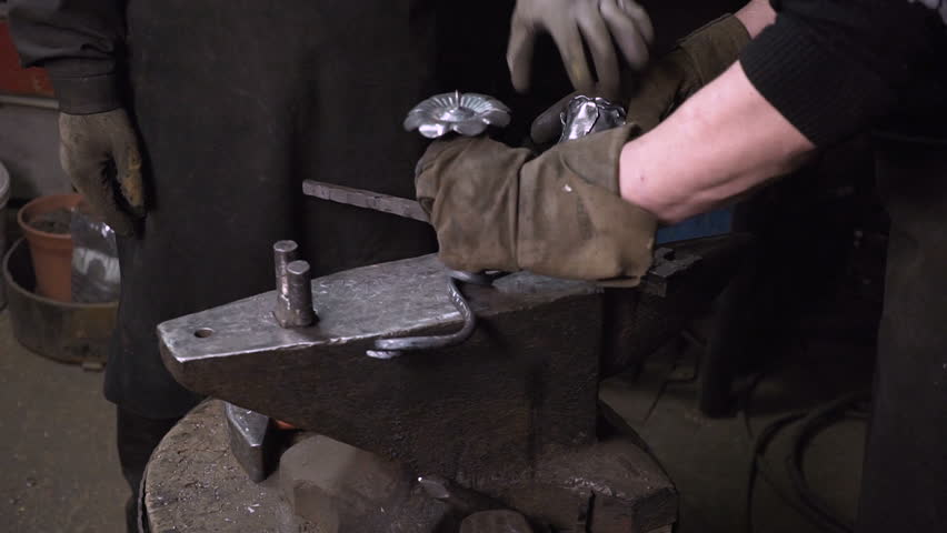 The blacksmith makes metal candle holder with rose and horseshoe. | Shutterstock HD Video #26871862