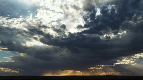 Sun rays beneath departing storm clouds at sunset, time lapse