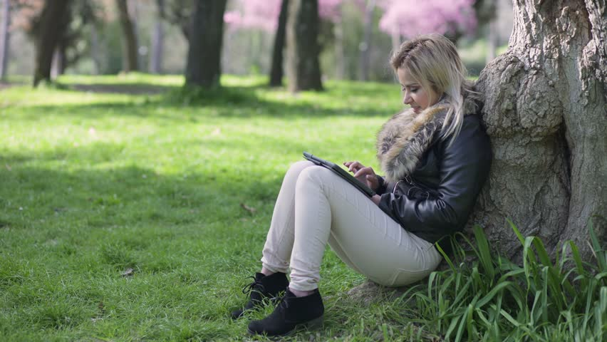 Young blond woman sitting under a tree while using the tablet   Shutterstock HD Video #26910532