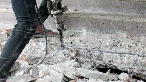 Worker using drilling machine, jackhammer to break the hard concrete floor in construction site
