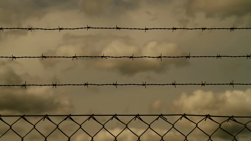 Barb wire fence with clouds behind
