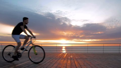 Young man with mountain bike on seafront during sunset or sunrise