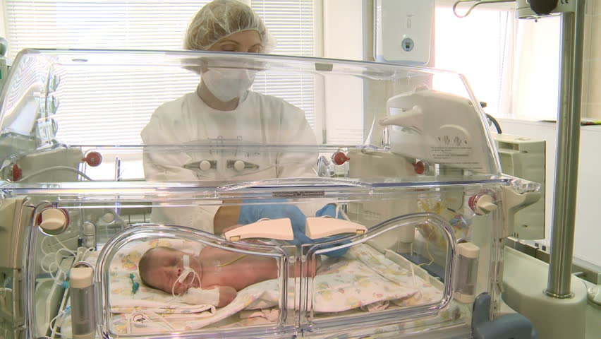 Russia. In October of 2015. Newborn baby lying in an incubator in intensive care in the hospital.Nurse of perinatal center cares .
