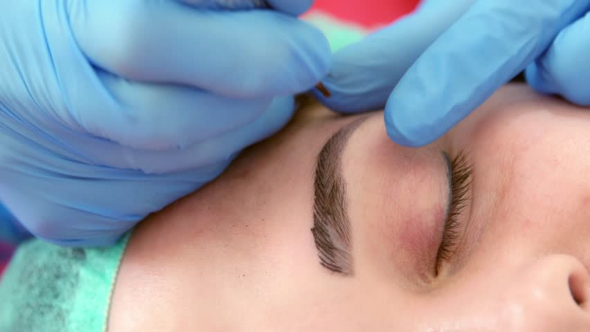 A close-up, a tattoo artist performs eyebrow tattooing, microblasting, a cosmetology room