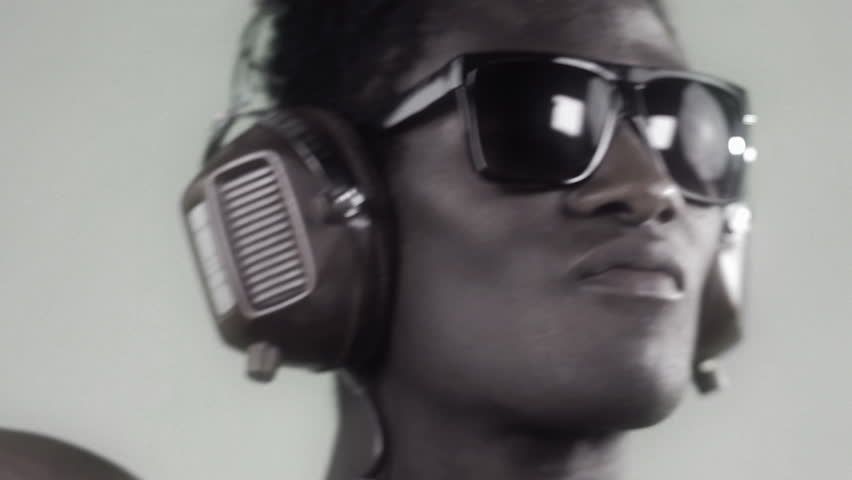 african cool guy dancing with headphones and glasses with a silver style