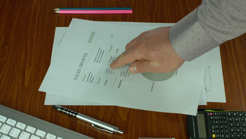 Two Businessmen Discussing Company Sales Data By Putting Documentation Sheets On A Brown Desk. They Point At Data In Order To Discuss The Data.  | Shutterstock HD Video #27059032