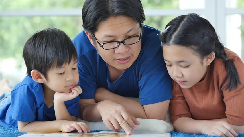 Happy Asian family reading book at home