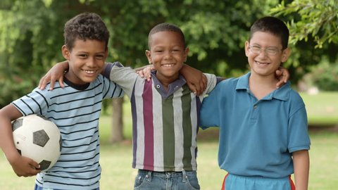 Young boys and sport, portrait of three happy young children with soccer ball smiling and looking at camera