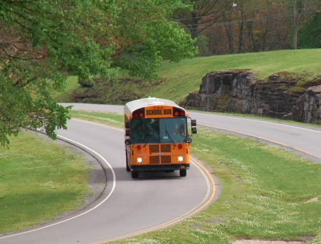 A big yellow school bus drives down the road DV NTSC video