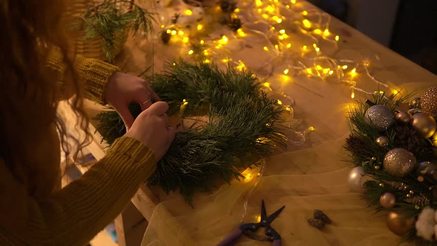 Woman making christmas wreath, top view