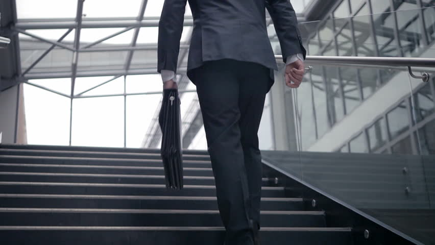 Slow motion of businessman climbing up the stairs in the office building. Confident man having a successful career in business.