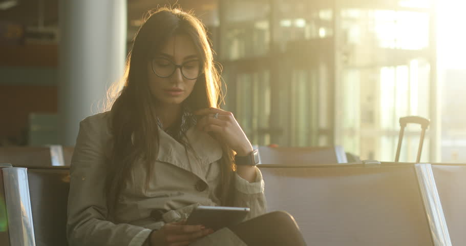 Pretty young female passenger browsing tablet with backpack and carry on luggage at international airport, Checking her smart watch | Shutterstock HD Video #27130432