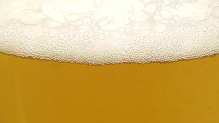 Close-up view of beer foam in a glass. Foam bubbles foam and burst. Full HD 1920x1080 Video Clip #27131092
