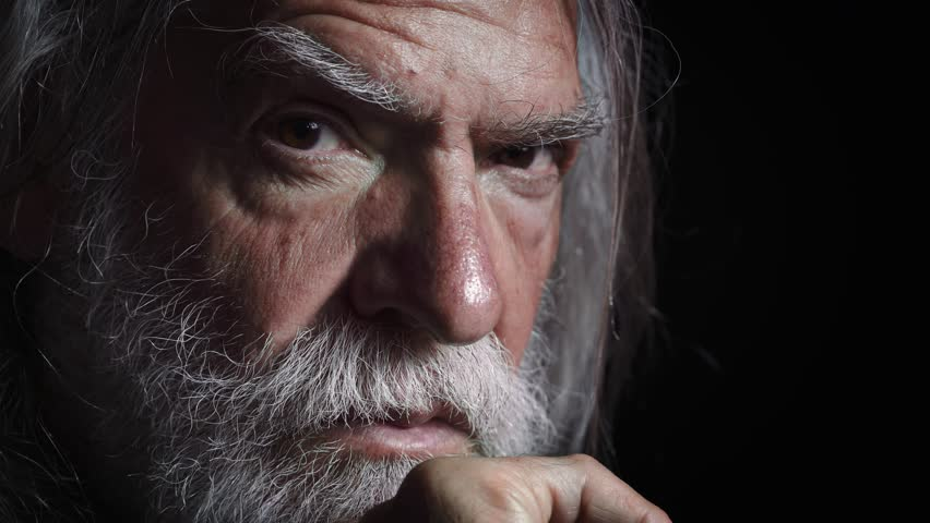 Old man with long white beard looks threatening the camera,darkness