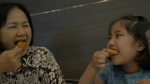 Slow motion of Asian child and senior woman enjoy eating fried chicken together