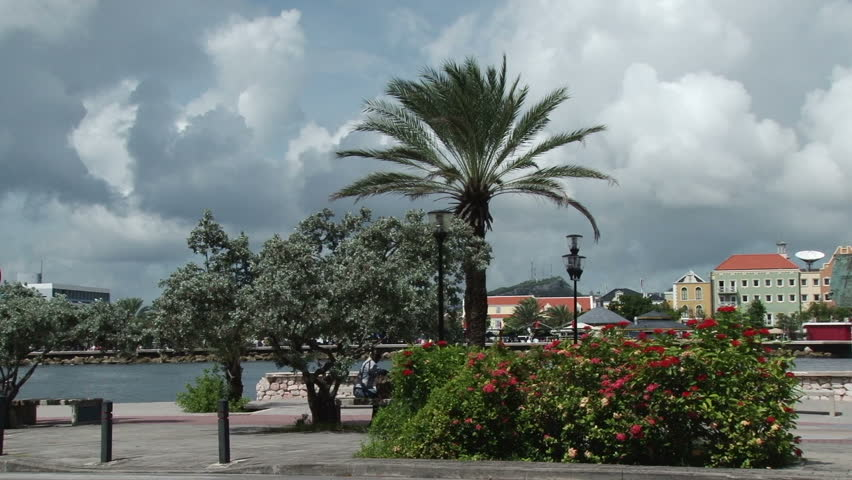 Pan across the waterfront of Willemstad, Curacao past a statue to the Queen Emma Bridge