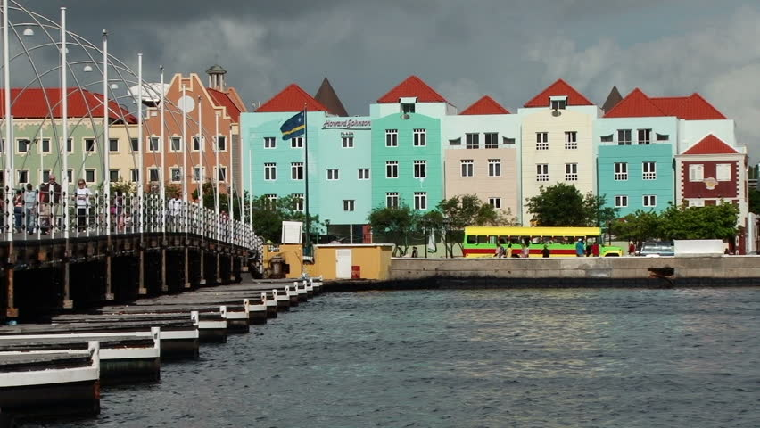 WILLEMSTAD/NETHERLANDS ANTILLES - 11 DECEMBER 2010: The Queen Emma Bridge and pretty colourful buildings in Willemstad Curacao. Taken early morning with people walking across the bridge