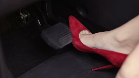 Woman in red high heels shoes pressing car pedals