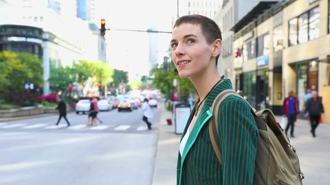 Woman in the city next to a busy road. Beautiful young woman with short hair, wearing a green jacket and bringing a backpack waiting to cross the street. Travel and lifestyle concepts.