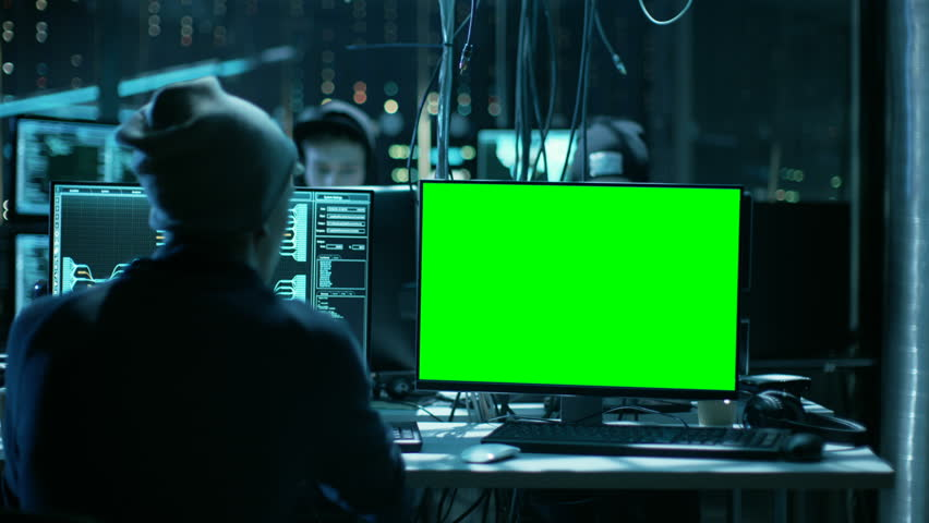 Team of Internationally Wanted Teenage Hackers with Green Screen Mock-up Display Infect Servers and Infrastructure with Ransomware. Their Hideout is Dark, Neon Lit and Has Multiple Displays.  | Shutterstock HD Video #27244642