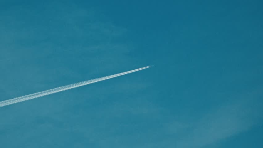 Flying jet airliner leaving contrain in the blue sky. 4K telephoto lens clip