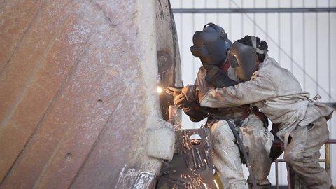 Welders repairing heavy equipment for the mining industry