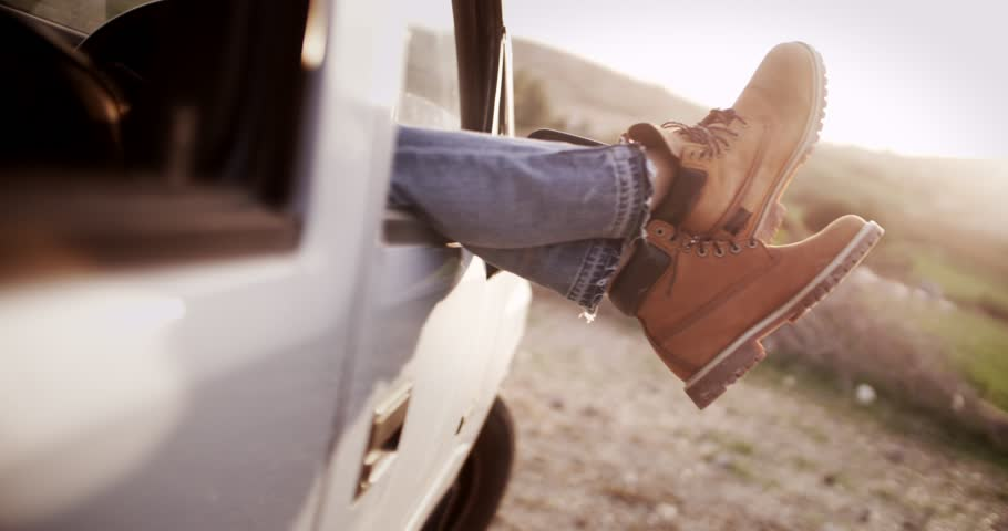 Women legs with boots sticking out of a car during camping trip in the country