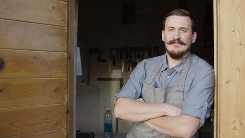 Portrait of 20s bearded woodworker looking at camera, stay behind workshop