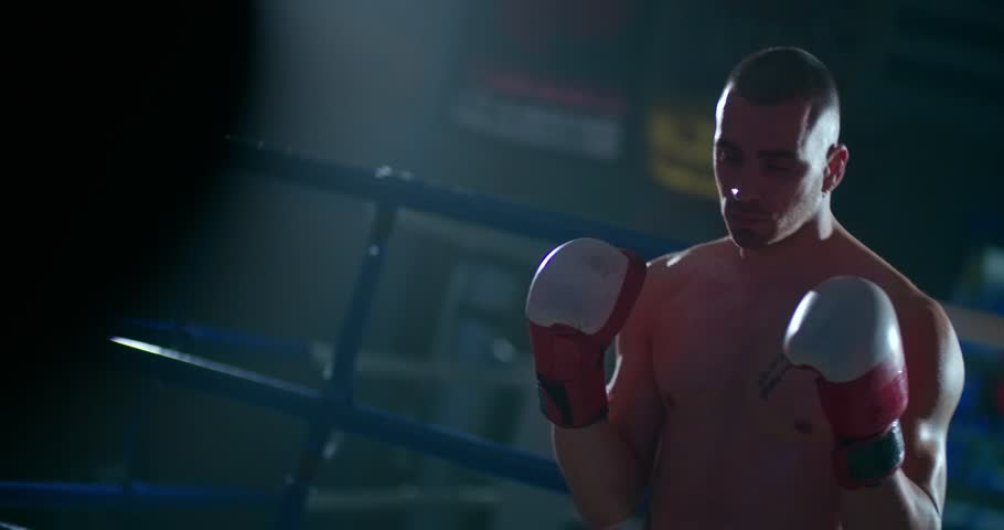 Male Muay Thai fighter standing in the boxing ring with boxing gloves ready to fight