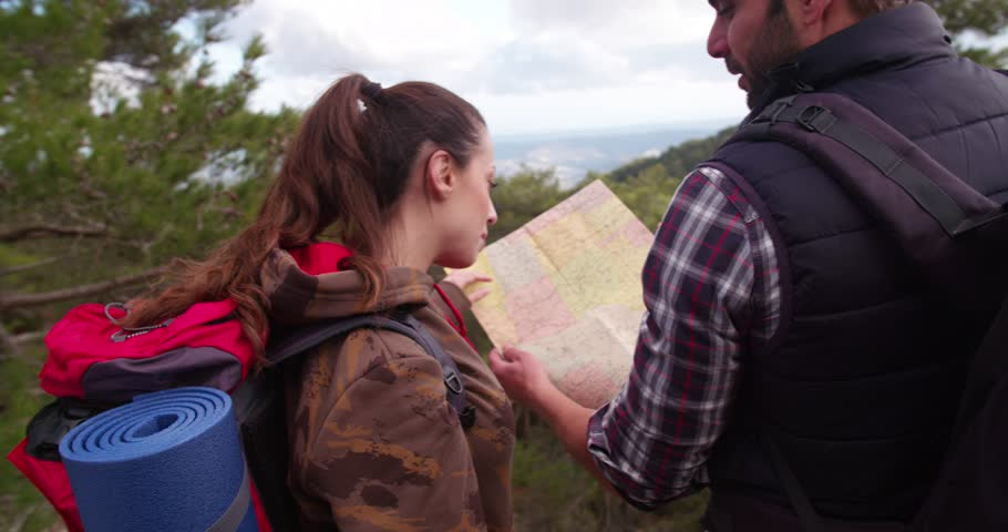 Young friends on a hiking adventrue standing on the mountain peak reading a map