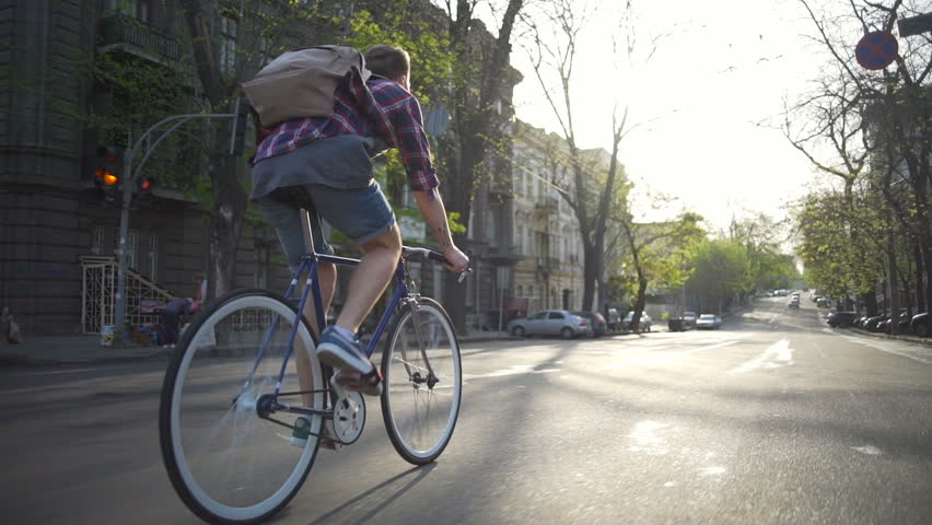 Man in a checkered shirt with a backpack riding his bike slow motion
