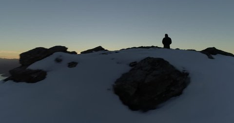Aerial footage lake reveal from snow capped mountain summit with a person standing at the peak. New Zealand in Autumn before sunset. 4K