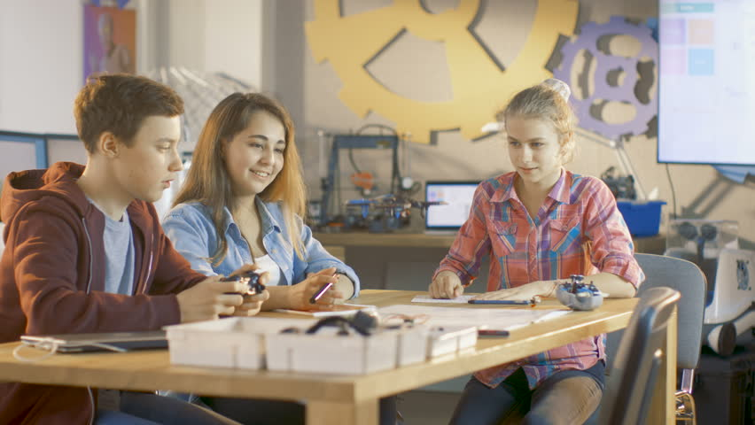 Boy Controls Mini Drone and Two Girls Watch. They're at School in Science Class on a Robotics Lesson. Shot on RED EPIC-W 8K Helium Cinema Camera.