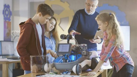 Teacher and His Pupils Work on a Programable Robot with LED Illumination for School Science Class Project. Shot on RED EPIC-W 8K Helium Cinema Camera.