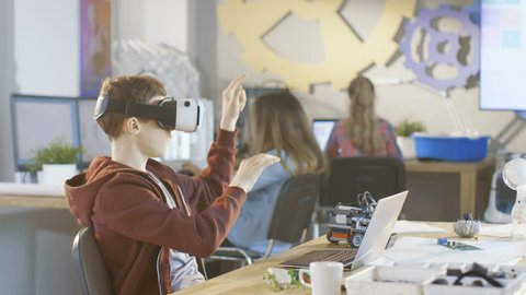 In a Computer Science Class Boy Wearing Virtual Reality Headset Works on a Programing Project. Shot on RED EPIC-W 8K Helium Cinema Camera.