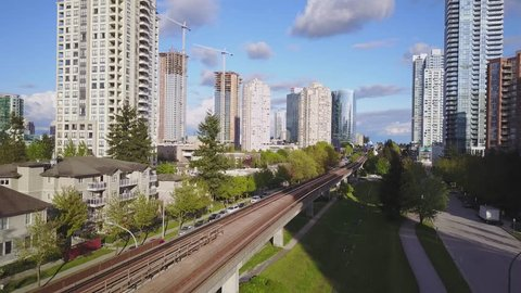 Aerial footage of Residential and Commercial Buildings in Metrotown Area, Burnaby, Vancouver, BC, Canada. Taken during a sunny evening. Pan Up