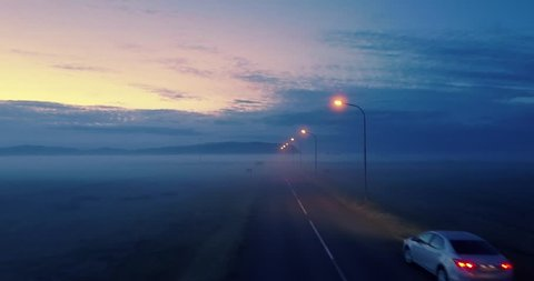 Lone car on remote highway road at twilight, aerial perspective with fog landscape in background. 4K UHD