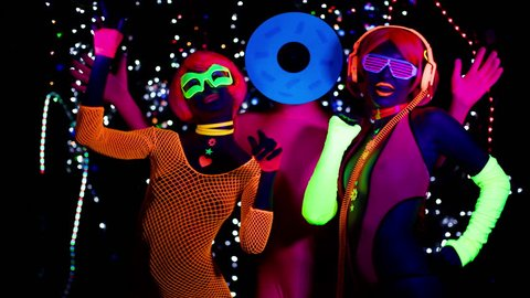 4k fantastic video of 3 sexy cyber glow ravers filmed in fluorescent clothing under UV black light. 2 cool women and a guy with a circular head