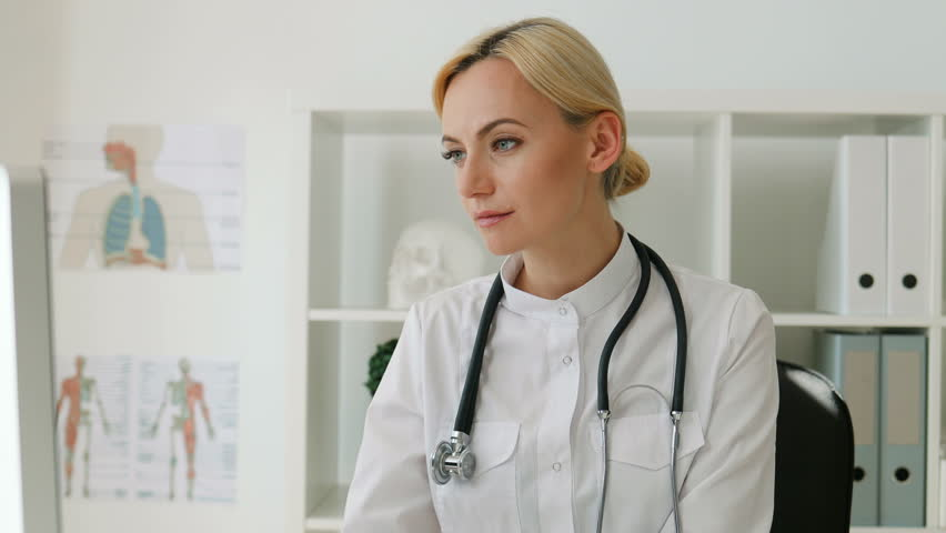 Portrait of young woman doctor with blond hair sitting at the desk using computer in office, turning to the camera and smiling.   Shutterstock HD Video #27385702