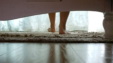 Woman getting out of the bed feet touching floor in the morning unveiling the curtains, camera under the bed