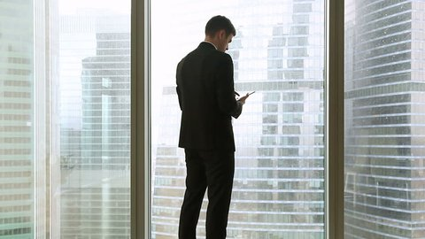 Rear view at thoughtful businessman in suit standing near full-length window of office holding using tablet, looking at big city buildings, waiting for meeting, making arrangement and chatting online