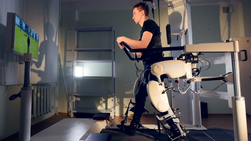 A patient during robot-assisted therapy with the Lokomat device. #27401362