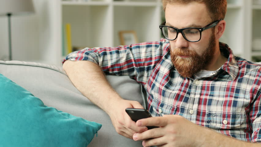 Attractive man with smartphone sitting on sofa at home in the living room and chatting with friends.