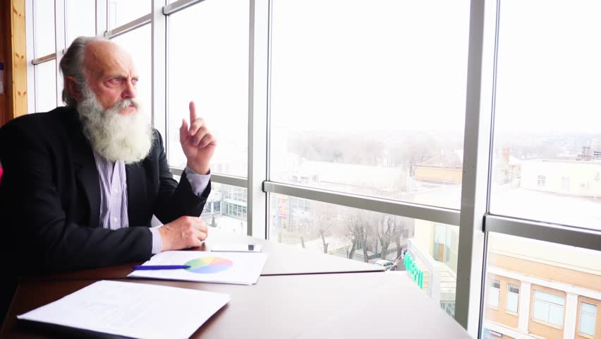 Retired Old Political Man Deal With Financial Matters in Office Looking at Window. Handsome Successful Grey Hair Man With Long Beard in Business Suit in Modernworkspace Thinks About Trending Supply   Shutterstock HD Video #27426721