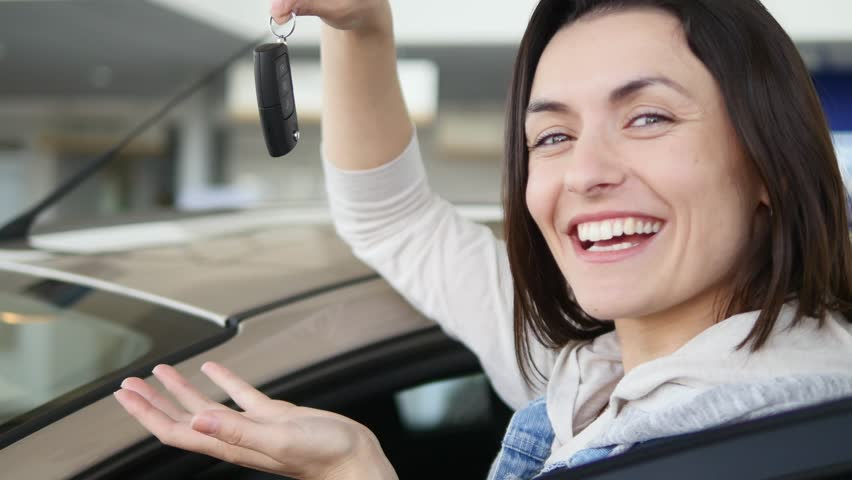 Happy woman showing the key of his new car. Auto business, car sale, technology and people concept - happy male with car dealer in auto show or salon.