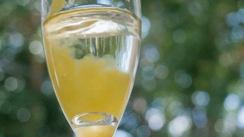 Orange juice pours into a glass of champagne making a mimosa cocktail at an outdoor bar. The alcoholic beverage is served during Sunday brunch as a bottomless option promoting day drinking and fun.